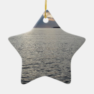 Warm sea sunset with cargo ship at the horizon christmas ornament
