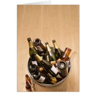 Waste bin full of empty champagne bottles on card