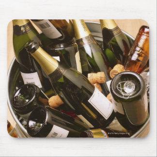 Waste bin full of empty champagne bottles on mouse mat