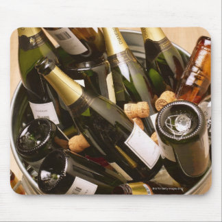 Waste bin full of empty champagne bottles on mouse pad