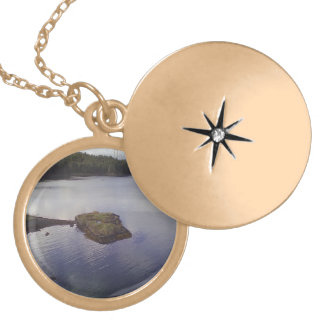 Water and a bridge in the background round locket necklace
