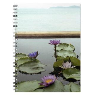 Water lilies in pond by ocean notebook