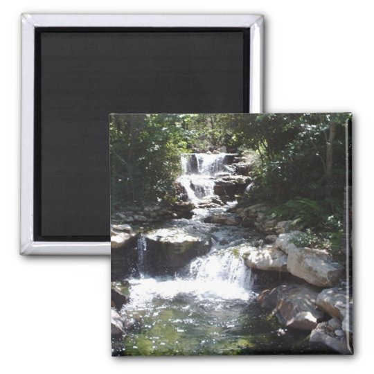 Waterfall streams over rocks into calm pool magnet