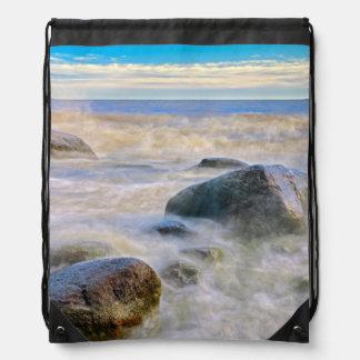 Waves crashing on shoreline rocks backpacks