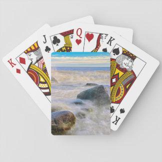 Waves crashing on shoreline rocks playing cards