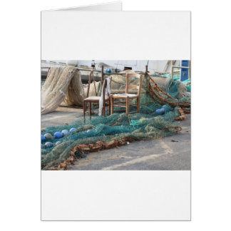 Weathered fishing nets on a harbor pier greeting card