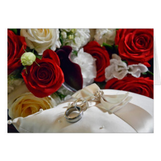 Wedding card with roses and ring pillow on front.