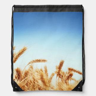 Wheat field against blue sky drawstring bag
