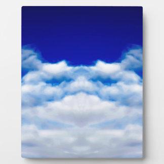 White cloud face against a blue sky plaque