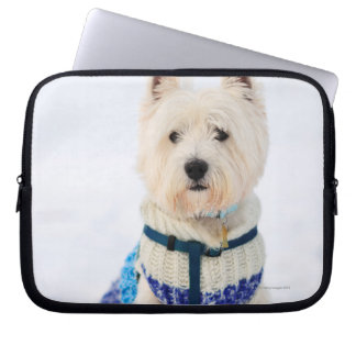 White dog in clothes in the snow. laptop sleeve