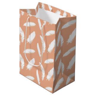 White feather print on soft peach medium gift bag