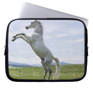white horse jumping on meadow laptop sleeve