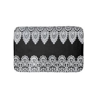 White lace forms a delicate border against black bath mats