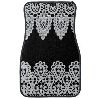 White lace forms a delicate border against black car mat