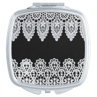 White lace forms a delicate border against black travel mirrors