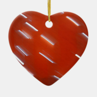 White LED light bulb on a red wall blurred in moti Ceramic Heart Decoration