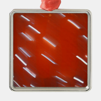 White LED light bulb on a red wall blurred in moti Silver-Colored Square Decoration