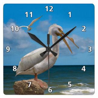 White Pelican on a Rock Wall Clocks