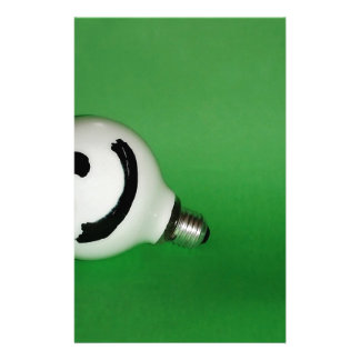 White smiling bulb on green background stationery paper