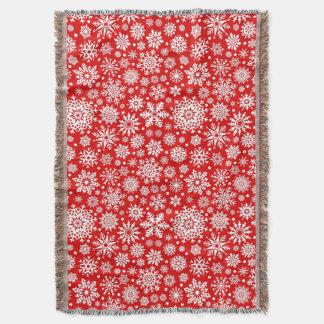 White snowflakes on red throw blanket