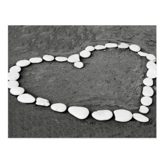 White stone heart in sand postcard