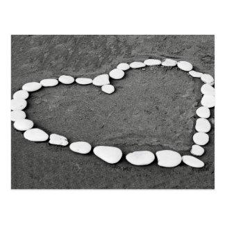 White stone heart in sand postcard