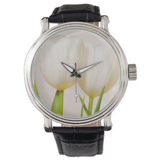 White tulips against a white background, wrist watches