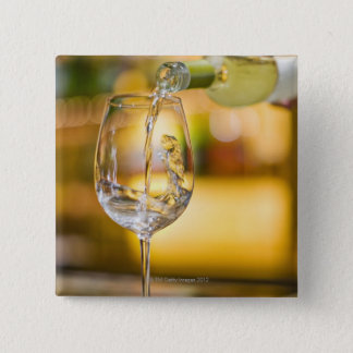White wine is poured from bottle in restaurant. 15 cm square badge