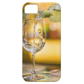White wine is poured from bottle in restaurant. case for the iPhone 5
