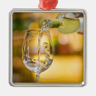 White wine is poured from bottle in restaurant. christmas ornament