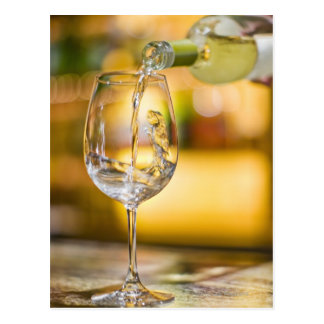 White wine is poured from bottle in restaurant. postcard
