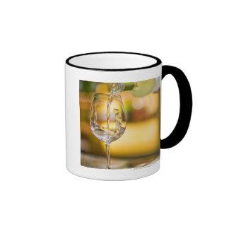 White wine is poured from bottle in restaurant. ringer mug