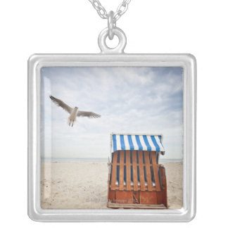 Wicker beach chair on beach silver plated necklace