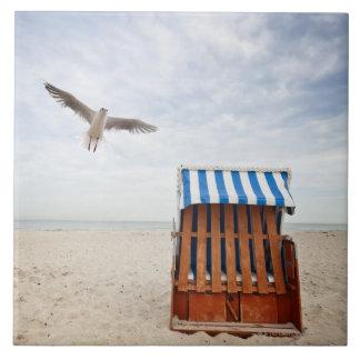 Wicker beach chair on beach tile