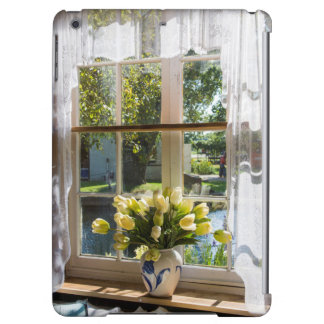 Window with lace curtain and tulips