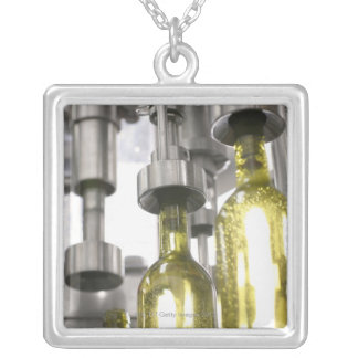 wine bottles being filled with wine at factory silver plated necklace