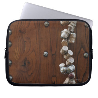 Wine corks hanging on wooden door laptop sleeve