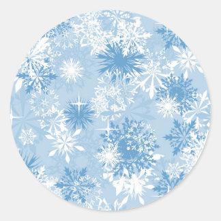 Winter snowflakes pattern on blue round sticker