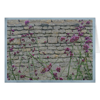 Wispy purple flowers on a rustic brick wall card