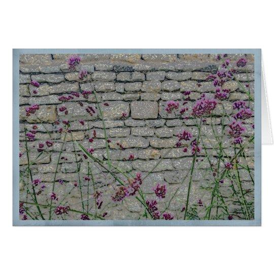 Wispy purple flowers on a rustic brick wall card