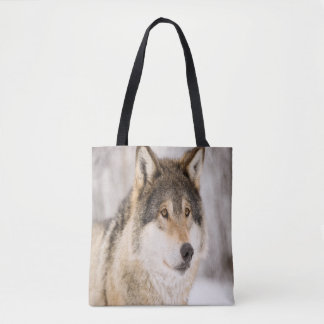 Wolf smiling in snow and winter forest tote bag