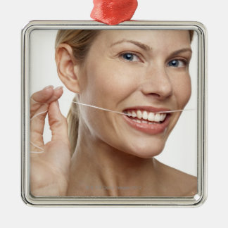Woman against white background flossing teeth, christmas ornament