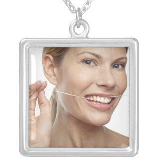 Woman against white background flossing teeth, custom jewelry