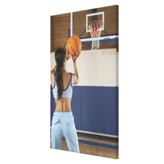Woman aiming at hoop with basketball, rear view canvas print