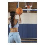 Woman aiming at hoop with basketball, rear view greeting card