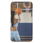Woman aiming at hoop with basketball, rear view iPod touch covers