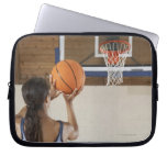 Woman aiming at hoop with basketball, rear view laptop computer sleeves