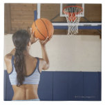 Woman aiming at hoop with basketball, rear view large square tile