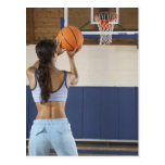 Woman aiming at hoop with basketball, rear view postcard
