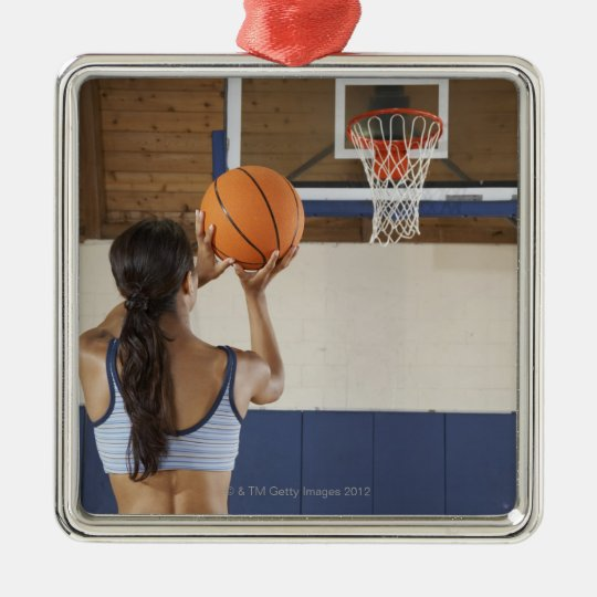 Woman aiming at hoop with basketball, rear view Silver-Colored square decoration